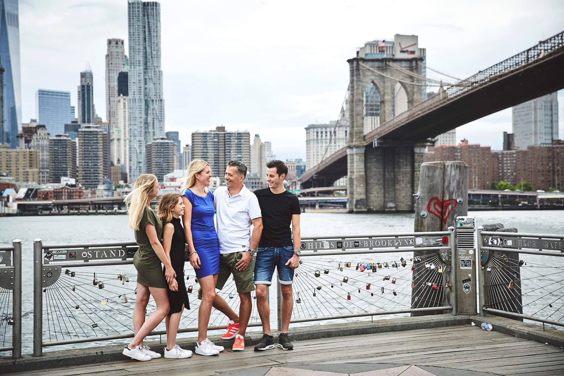 Family laughing together at pier with the Brooklyn Bridge in the background in Brooklyn, New York City USA