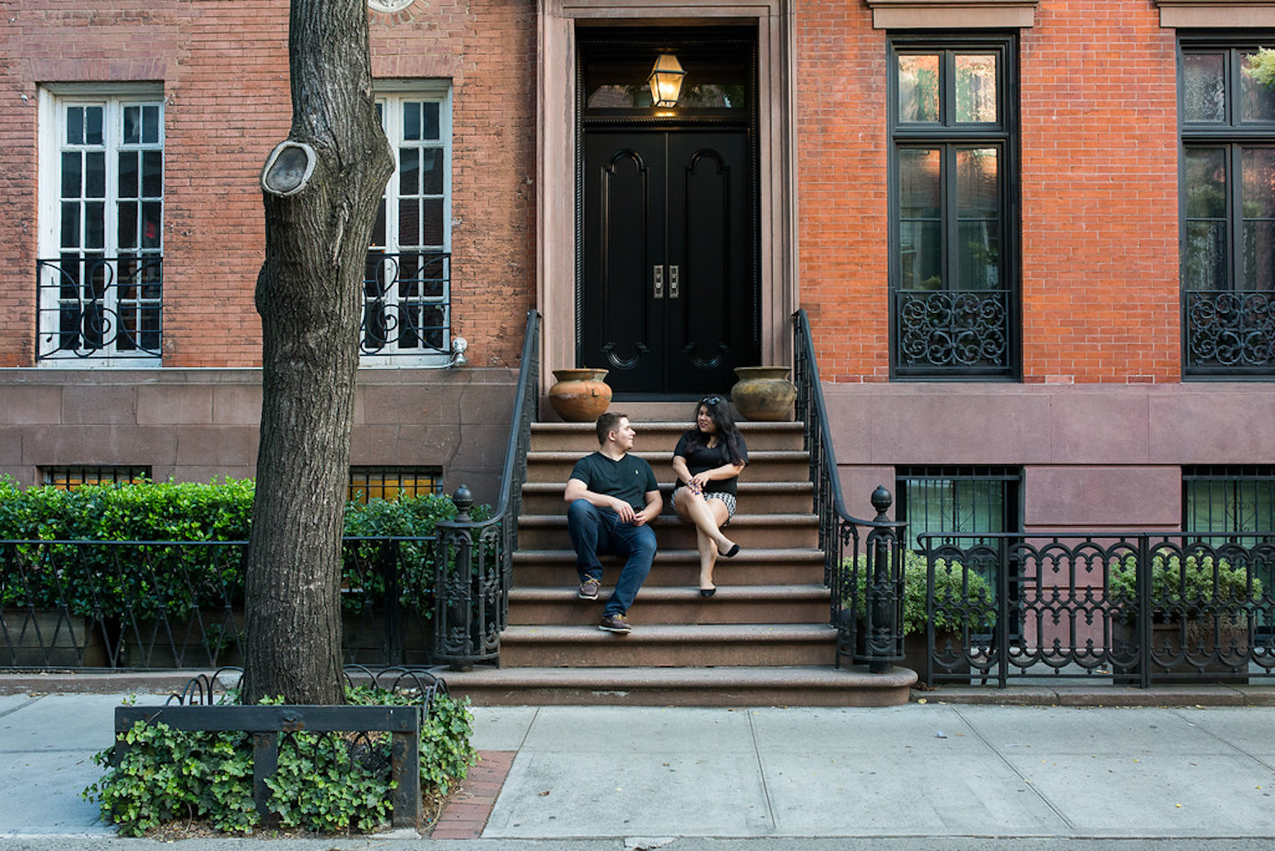 Couple sitting on steps and looking at each other in Greenwich Village, New York City USA