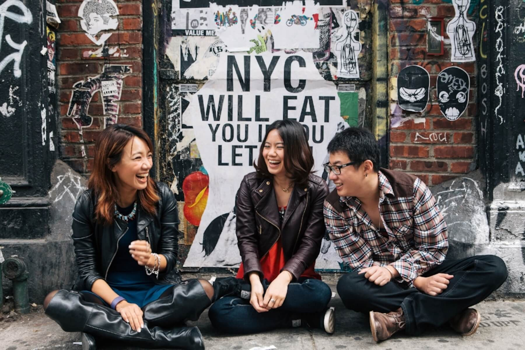 Three friends sitting on the ground together and laughing in front of a graffiti wall in New York City, USA