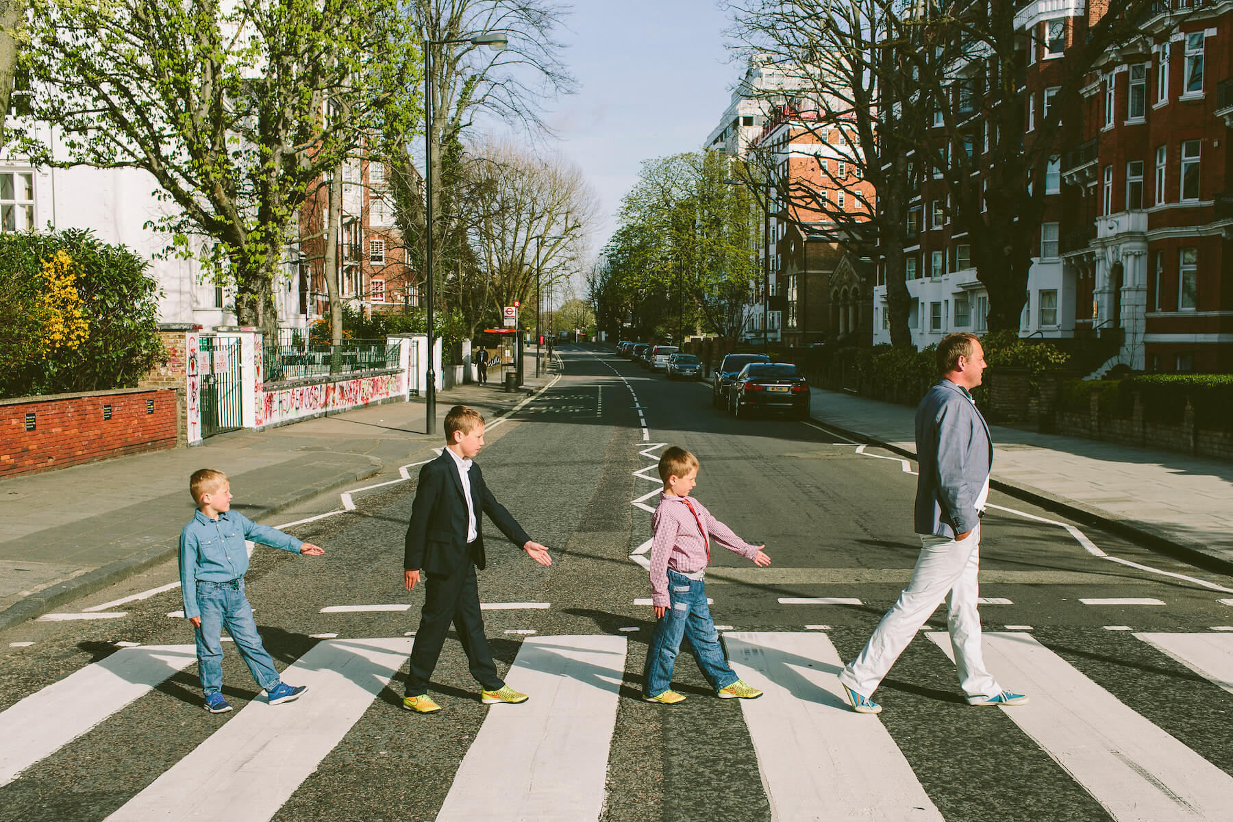 Father and three young sons crossing the road on Abbey Road on a family trip in London, UK