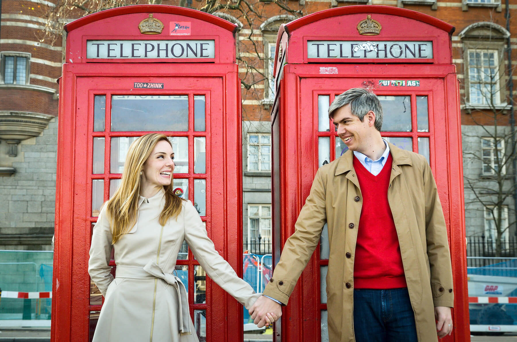 Couple holding hands and standing in front of iconic red telephone booths in London, UK
