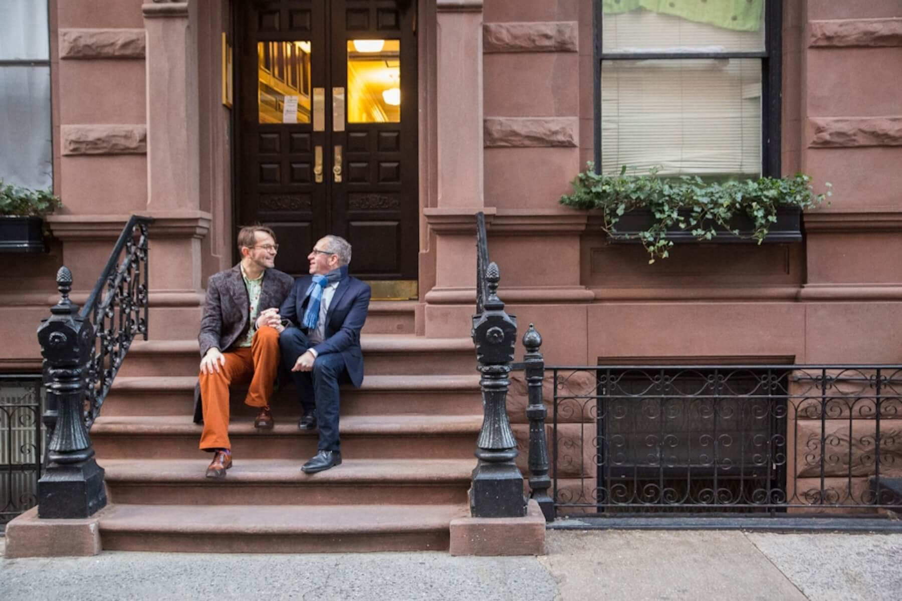 LGBTQ+ couple sitting together and holding hands on steps in Greenwich Village, New York City USA
