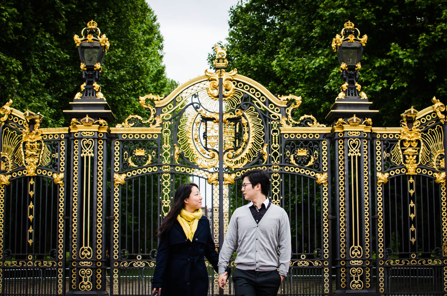 Asian couple looking at each other lovingly in front of the Buckingham Palace golden gates in London, UK