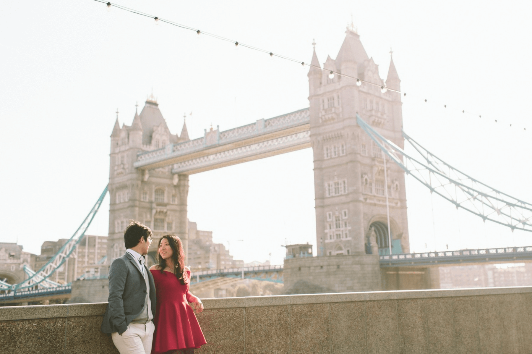 Asian couple looking at each other lovingly with the Tower Bridge in the background in London, UK