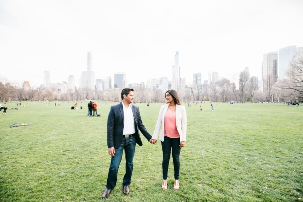 Couple holding hands and smiling at each other in the great lawn in Central Park in New York City, New York USA