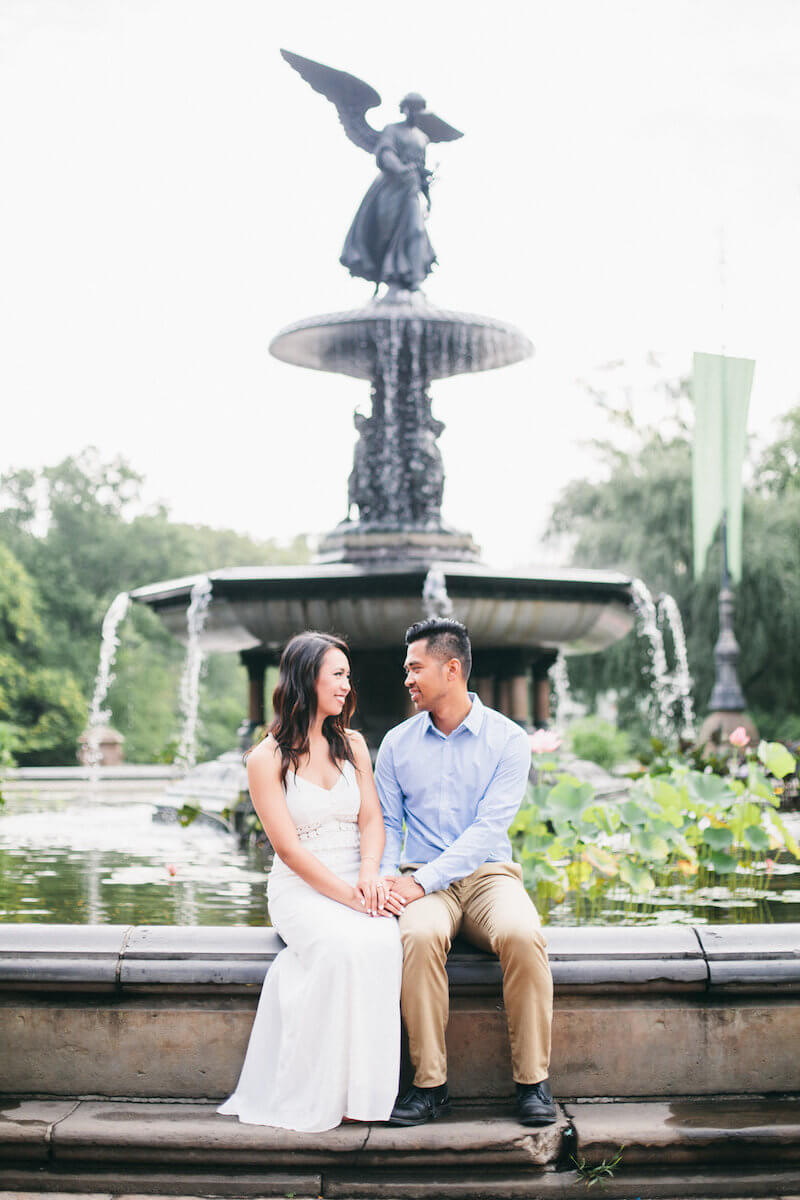 Asian couple smiling and holding hands while sitting on the edge of Bethesda fountain in Central Park, New York City USA