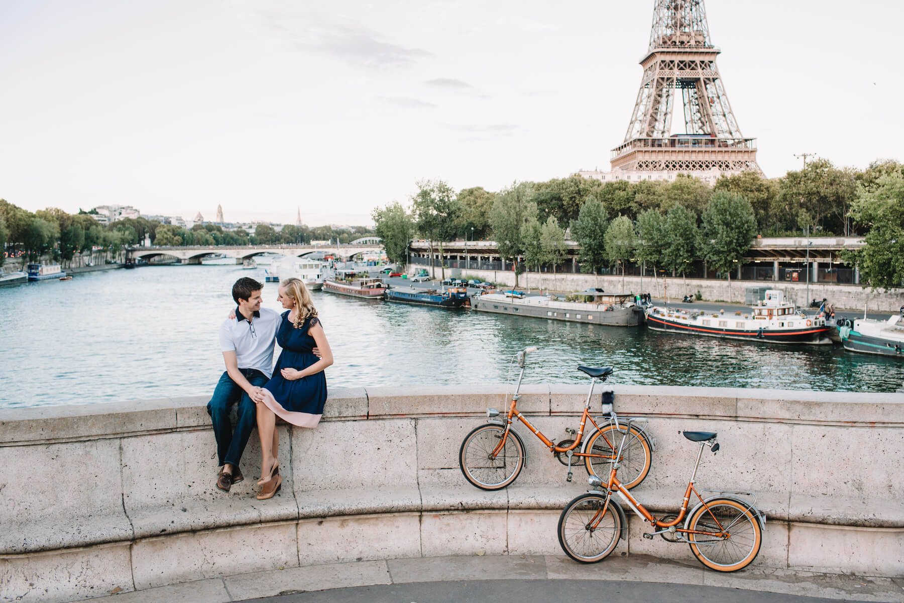 a couple sitting on a ledge, she is pregnant and holding her belly in front of the Eiffel Tower in Paris, France