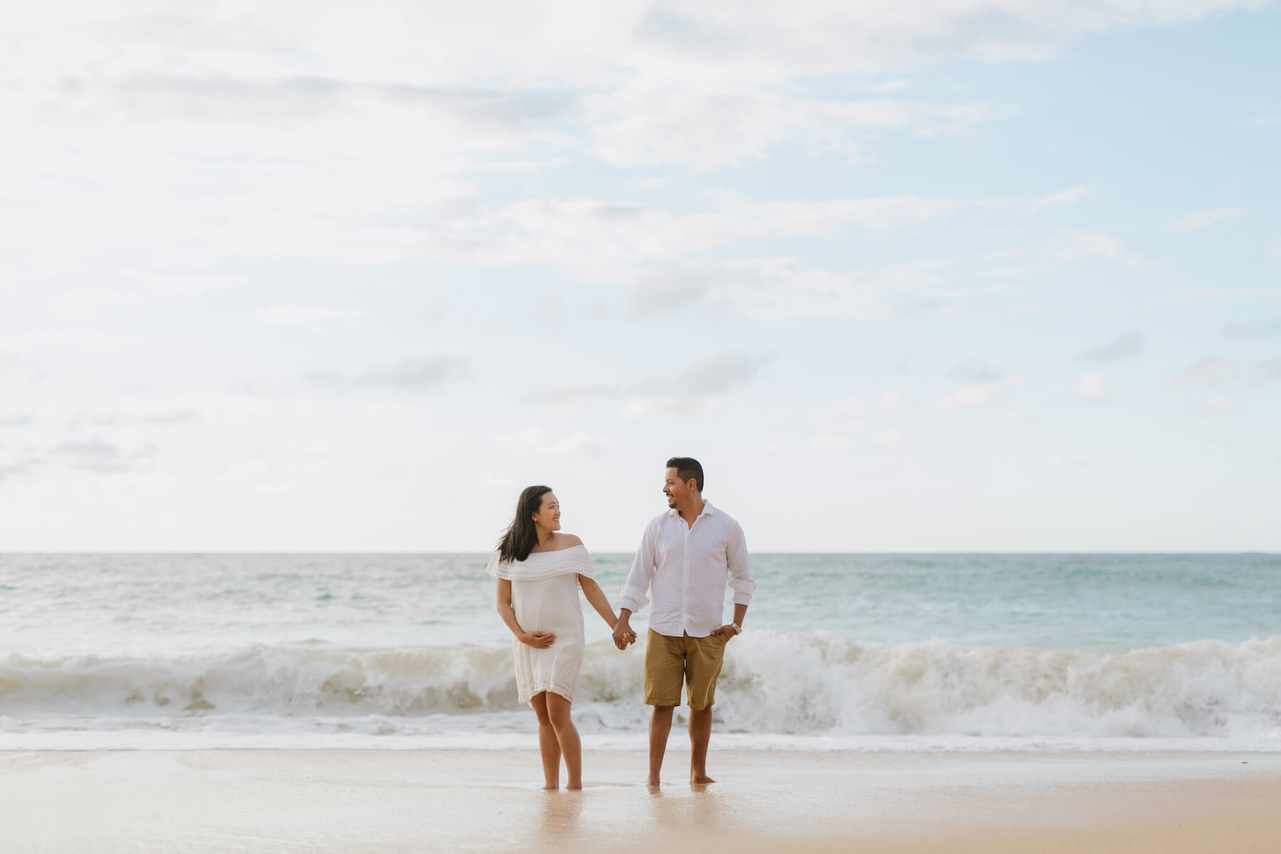 pregnant couple standing on the beach in Maui, Hawaii