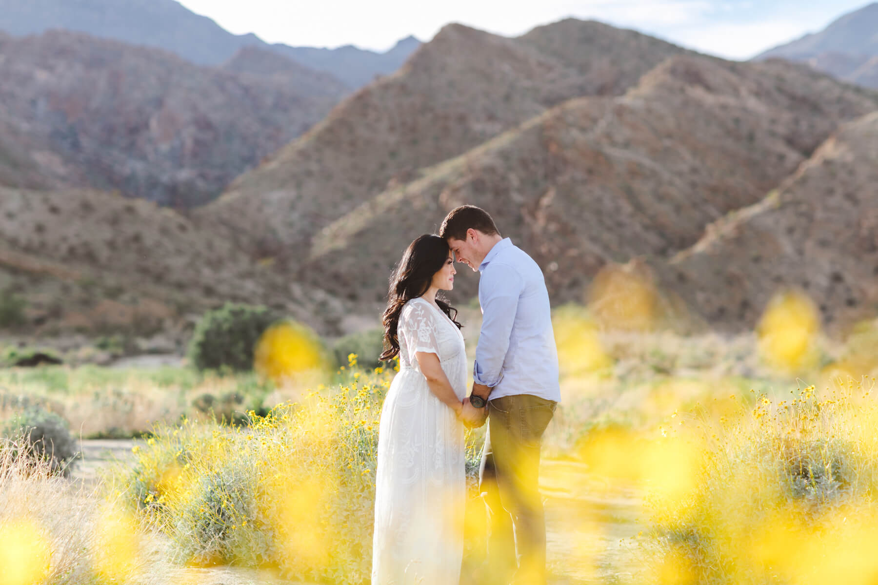 pregnant couple looking at each other in the desert in Palm Spring, California
