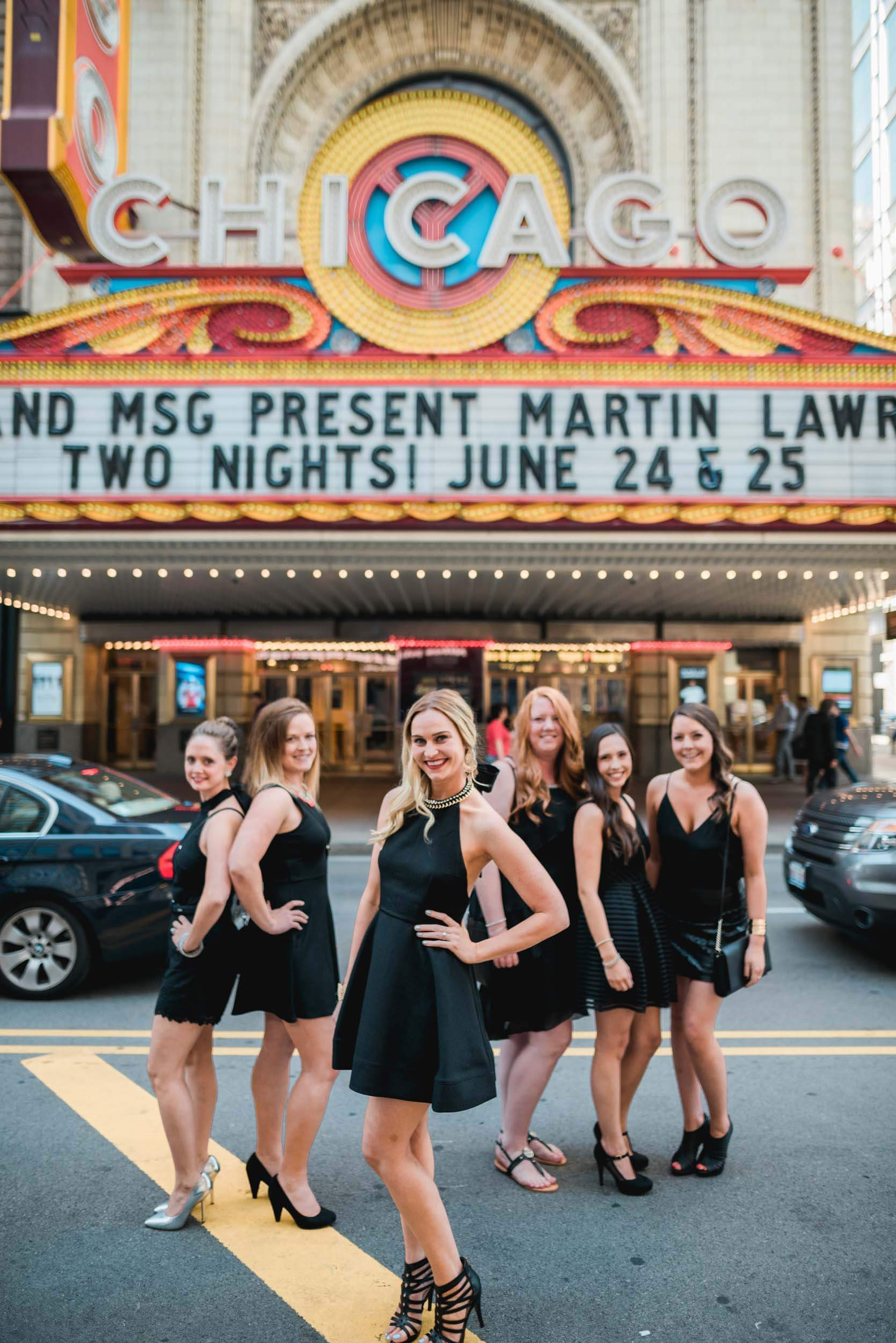 Six female friends on a bachelorette trip together in front of the Chicago theatre in Chicago, USA