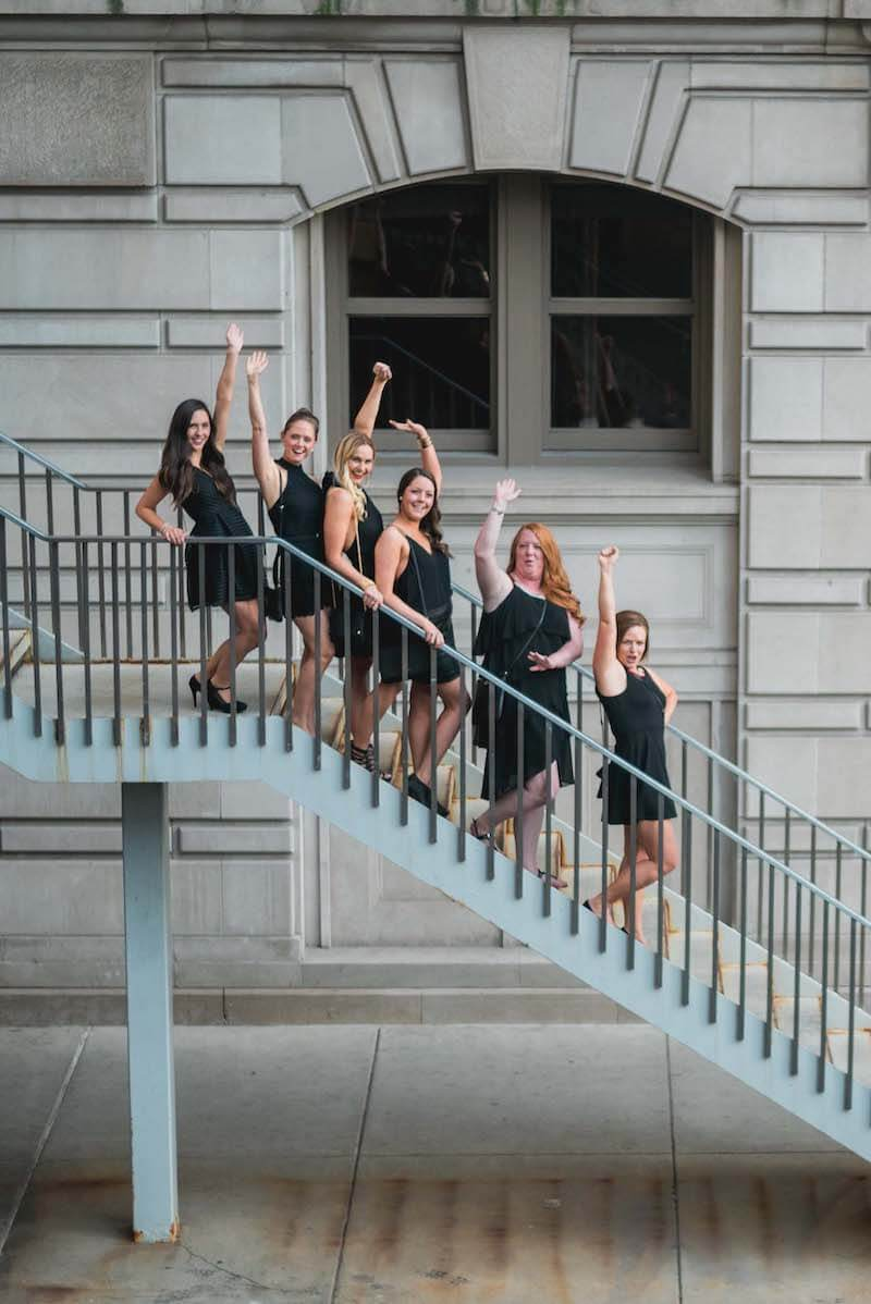 Six female friends on a bachelorette trip standing on some stairs raising their hands in the air in Chicago, USA