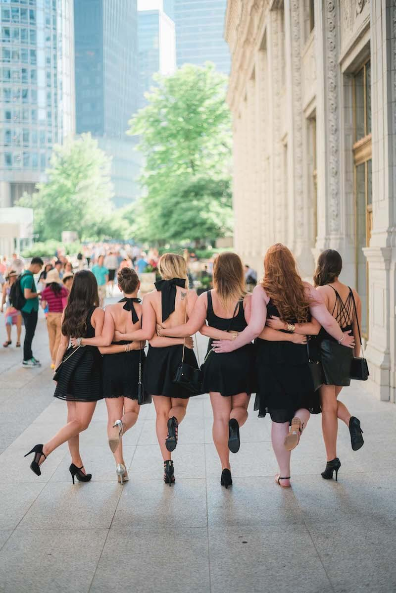 Six female friends on a bachelorette trip walking together with their arms around each other's waists in Chicago, USA