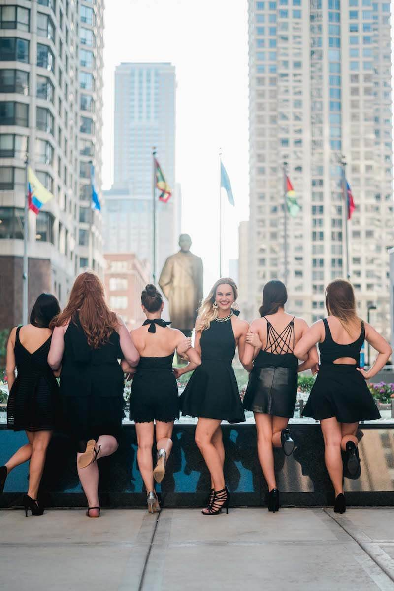Six female friends on a bachelorette trip standing in front of a fountain with 5 woman facing away and 1 woman facing the camera in Chicago, USA