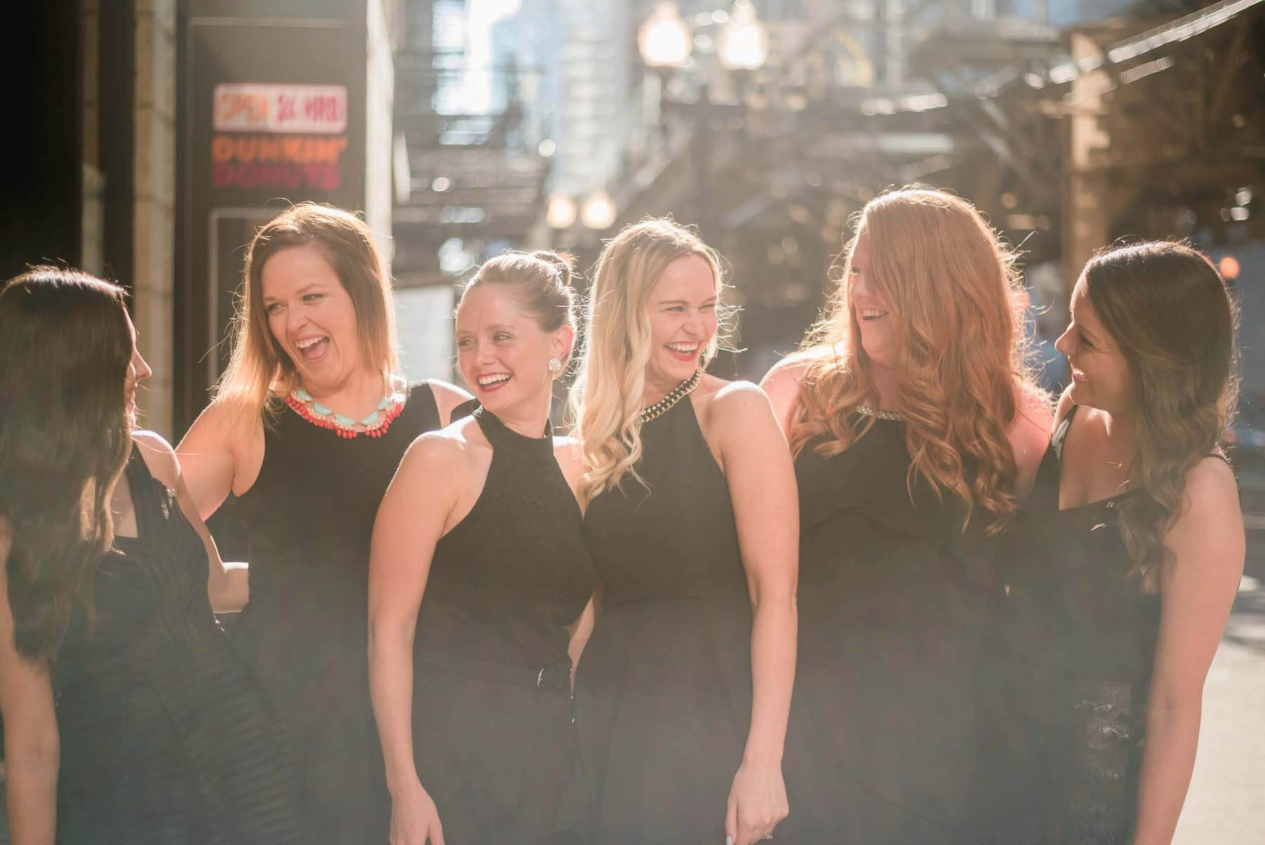 Six female friends standing together laughing with one another on a bachelorette trip in Chicago, USA