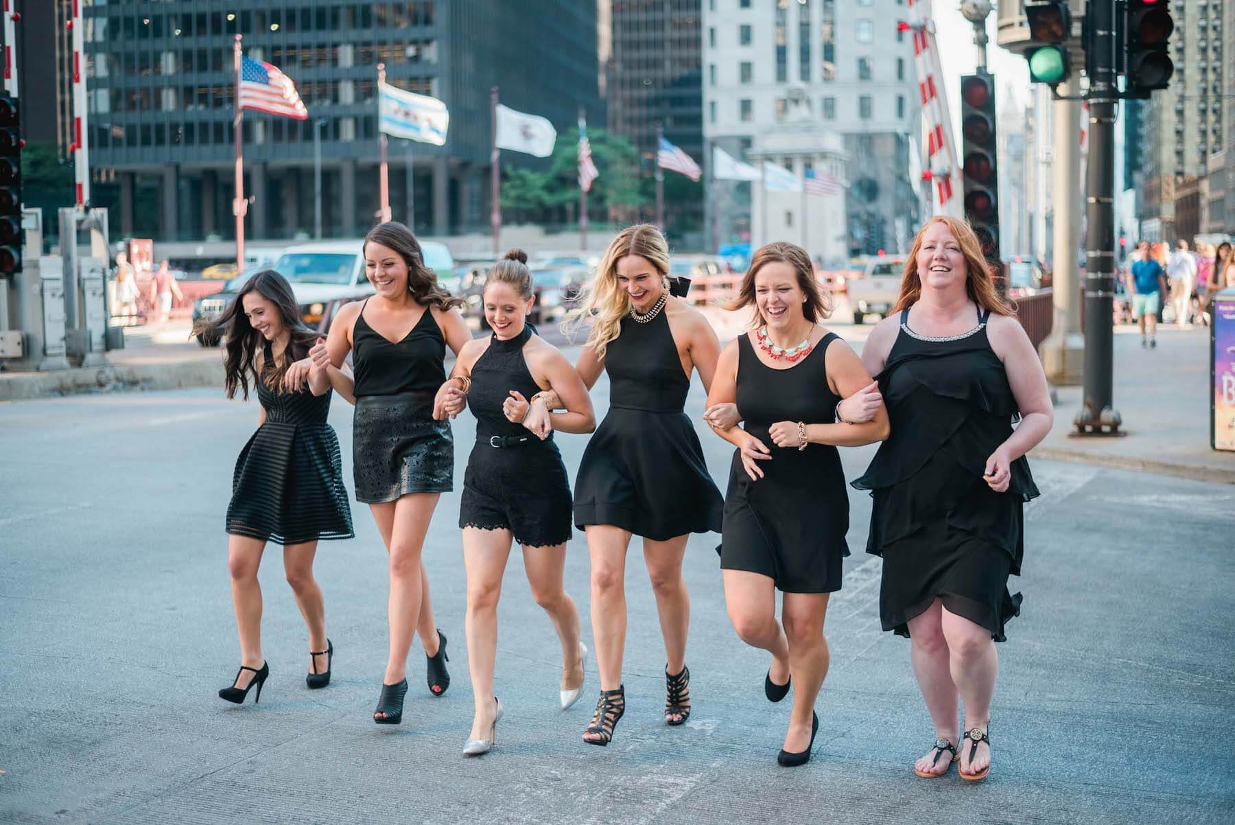 Six female friends crossing the street and holding hands on a bachelorette trip in Chicago, USA