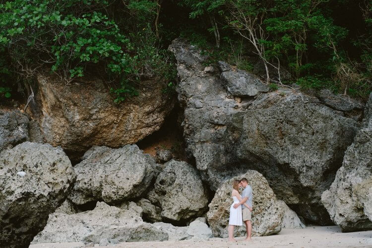 Couple hugging in front of a large rock wall at Seminyak Beach, Bali