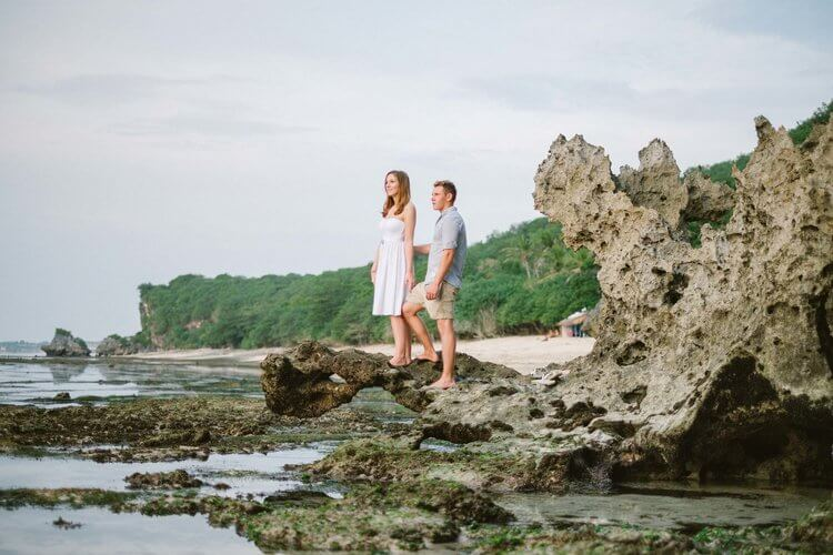 Couple standing at a rocky shore overlooking the sea at Seminyak Beach, Bali