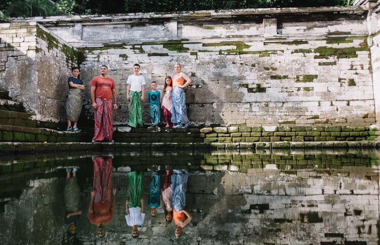 Family of six at Ubud Temple standing along the prayer bathing pools in Ubud, Bali Indonesia