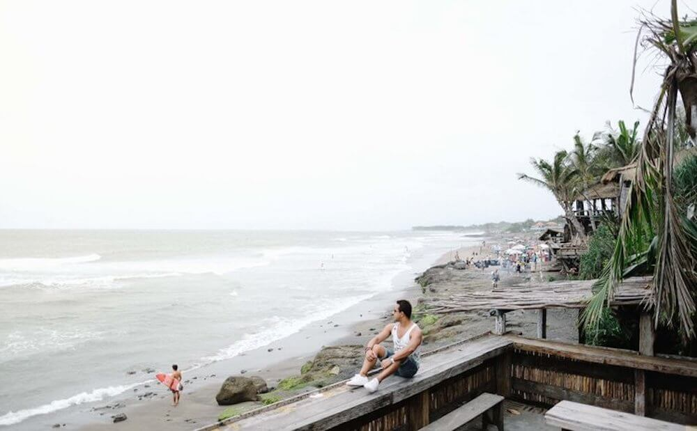 Man sitting on wall ledge overlooking the surf waves at Seminyak Beach, Bali