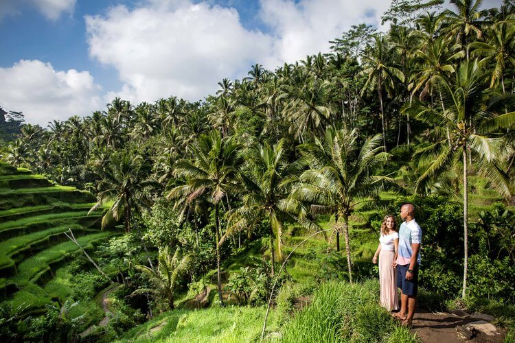 Couple standing in rice paddy fields on a couples trip in Ubud, Bali Indonesia