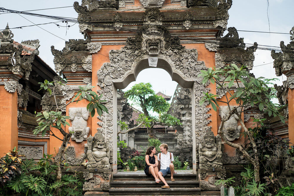 Couple sitting on steps outside of Ubud Temple in Ubud, Bali Indonesia