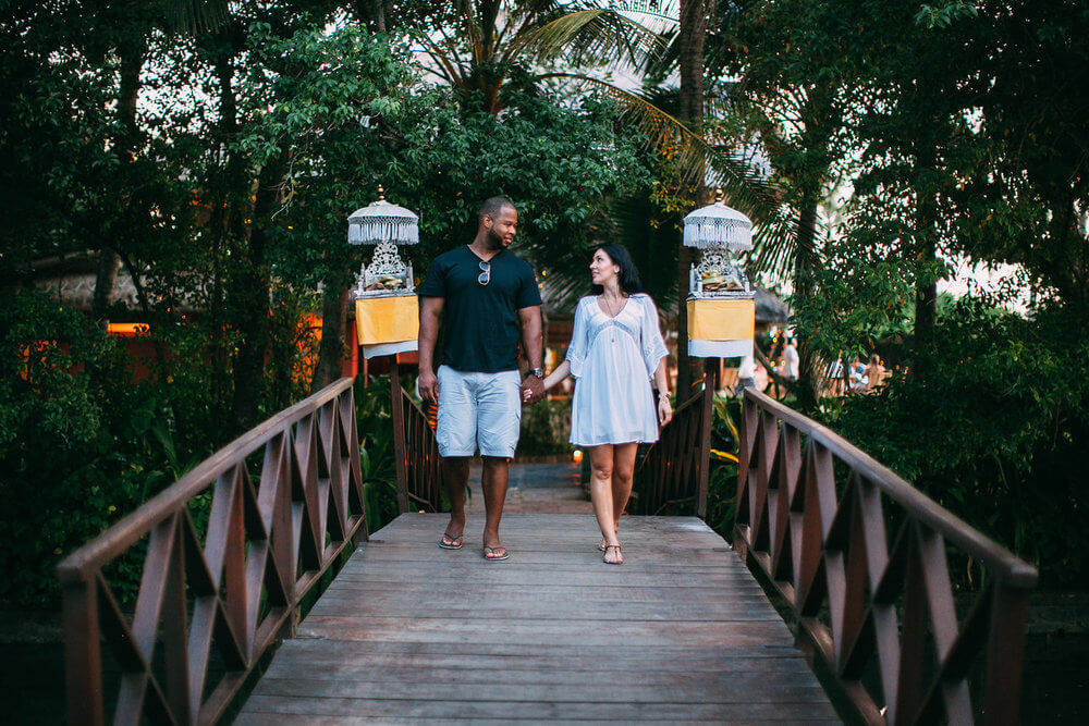 Couple holding hands and walking across a bridge at Seminyak Beach, Bali