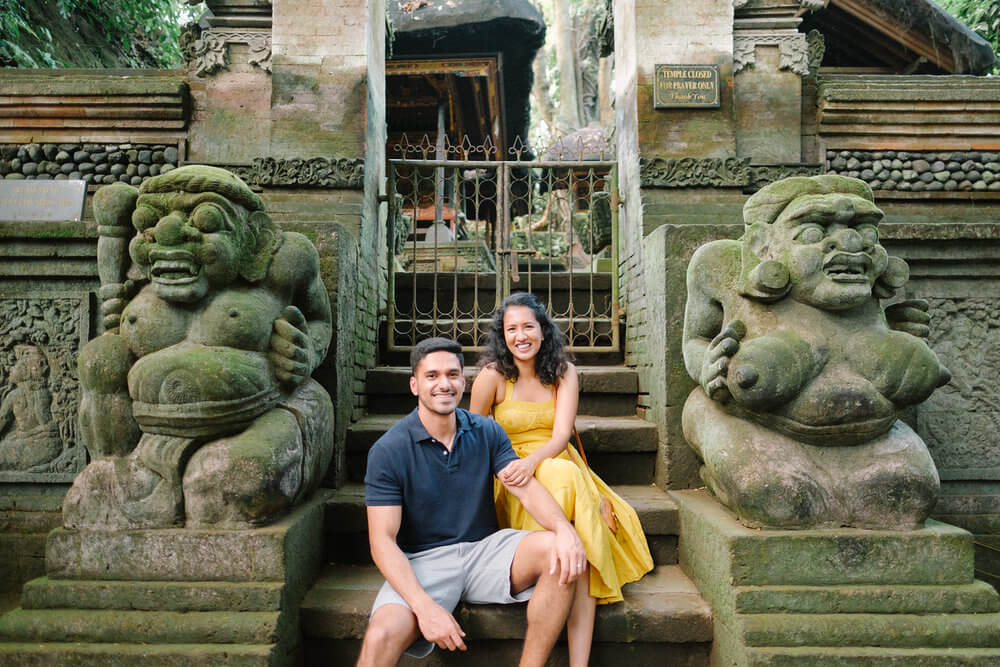 Couple sitting on steps outside of a small temple in the Monkey Forest in Bali, Indonesia