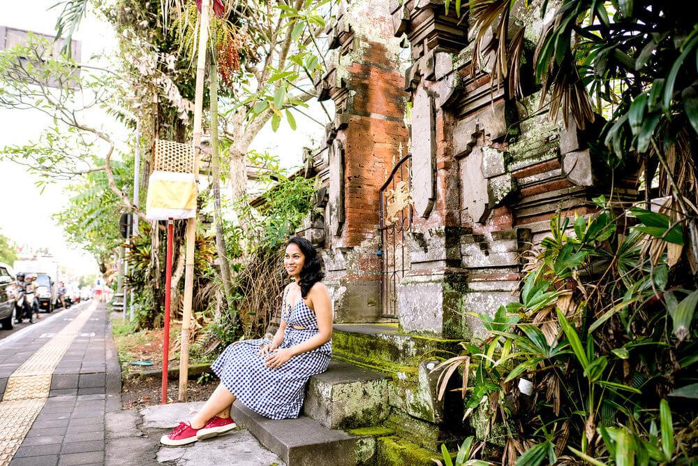 Woman sitting on steps outside of Ubud Palace in Ubud, Bali Indonesia