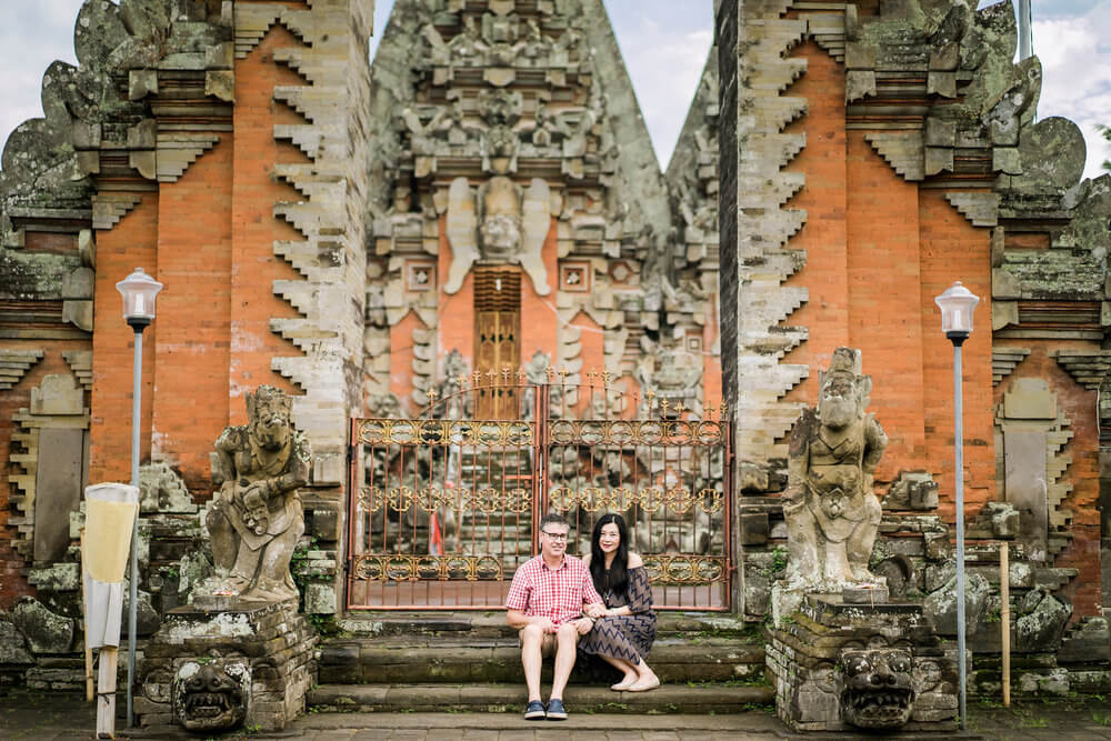 Couple sitting on steps outside of a temple in Bali Indonesia