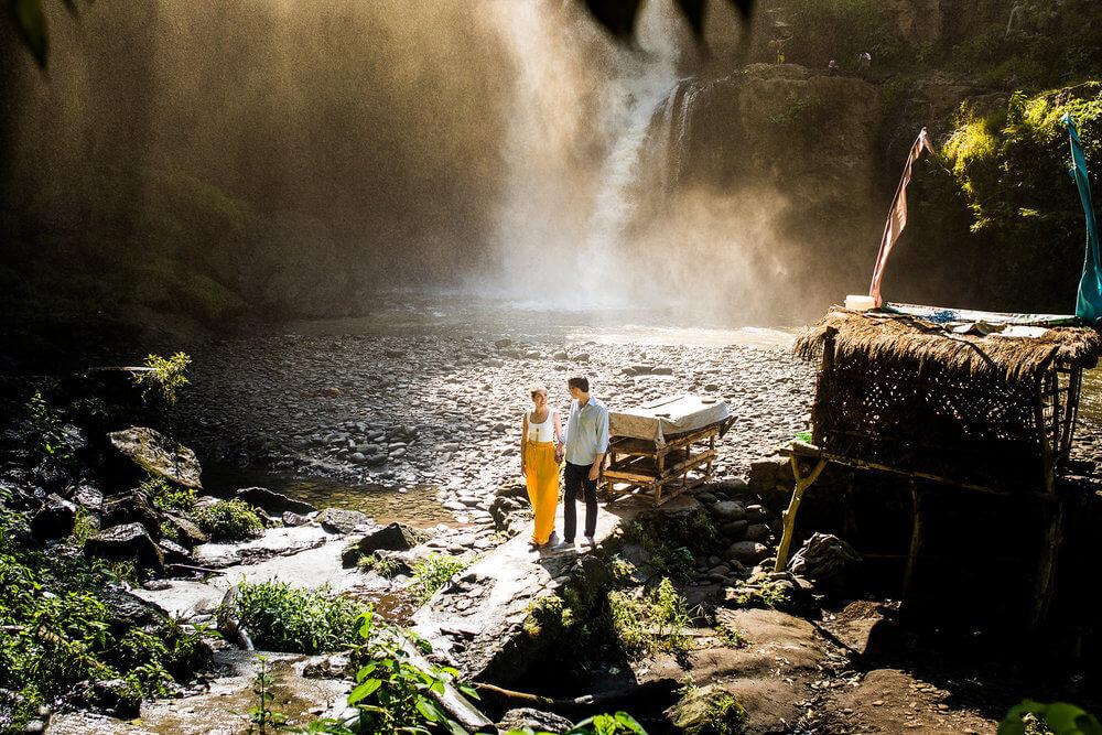 Couple walking along shoreline of water of the Tegenungan Waterfall in Bali Indonesia