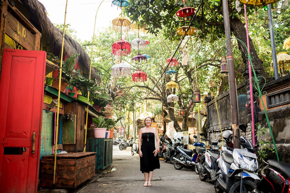 Woman standing in an colourful alleyway on a solo trip in Ubud, Bali Indonesia