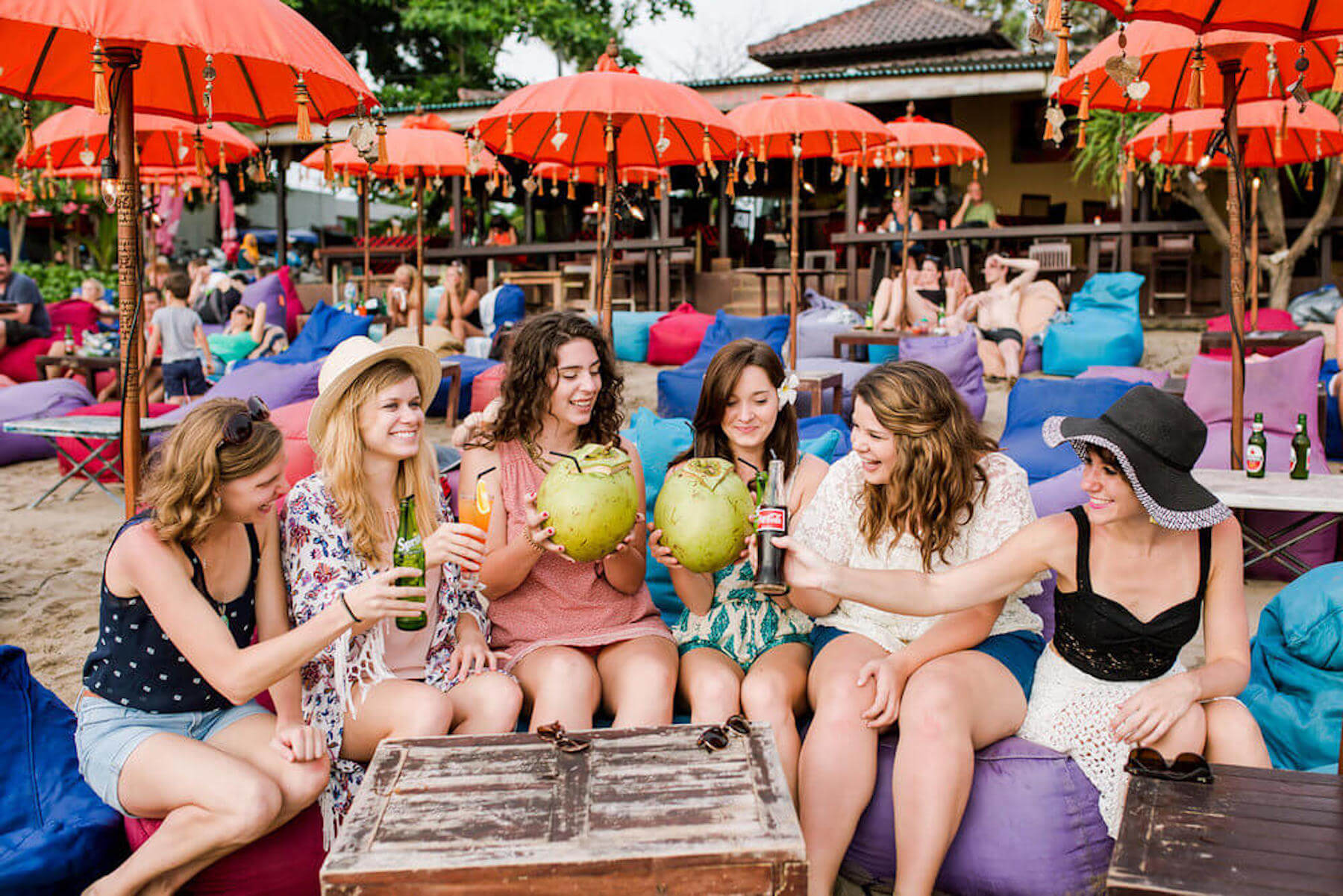 Six woman sitting together and cheering their drinks at Seminyak Beach, Bali