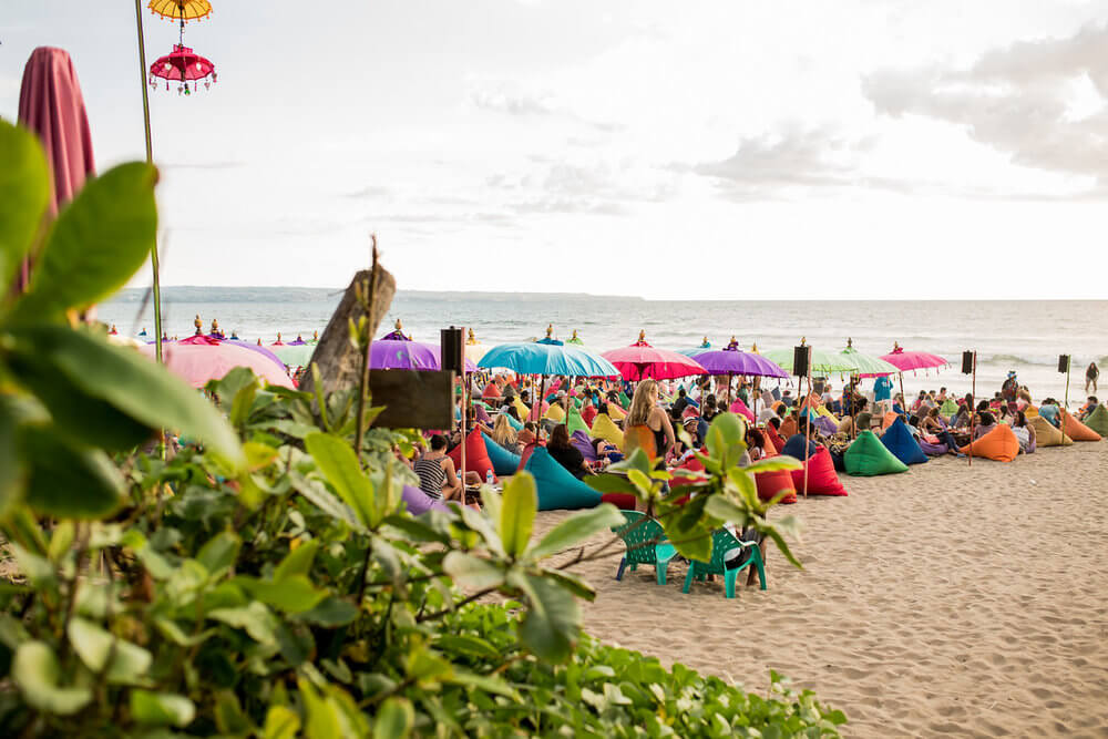 Large group of people on the beach sitting on bean bag chairs beneath umbrellas on Seminyak Beach, Bali