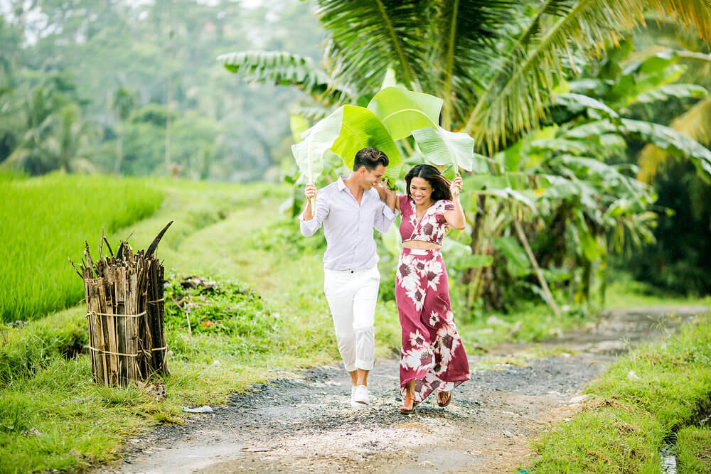 Couple using giant leaves as an umbrella to run out of the rain on a couples trip in Ubud, Bali Indonesia