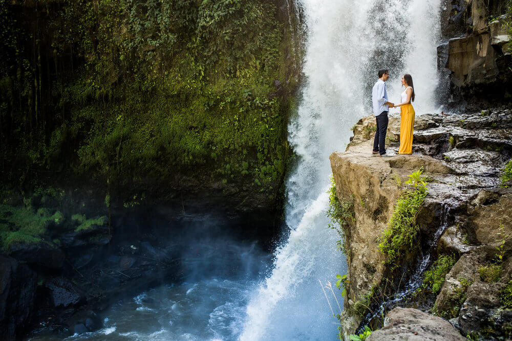 Couple standing near cliffside with the Tegenungan Waterfall in the background in Bali, Indonesia