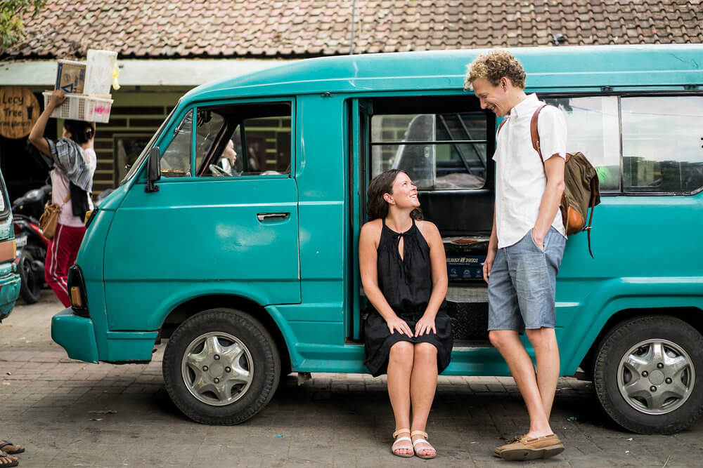 Woman sitting in a Westfalia van looking up at her partner in Ubud, Bali Indonesia