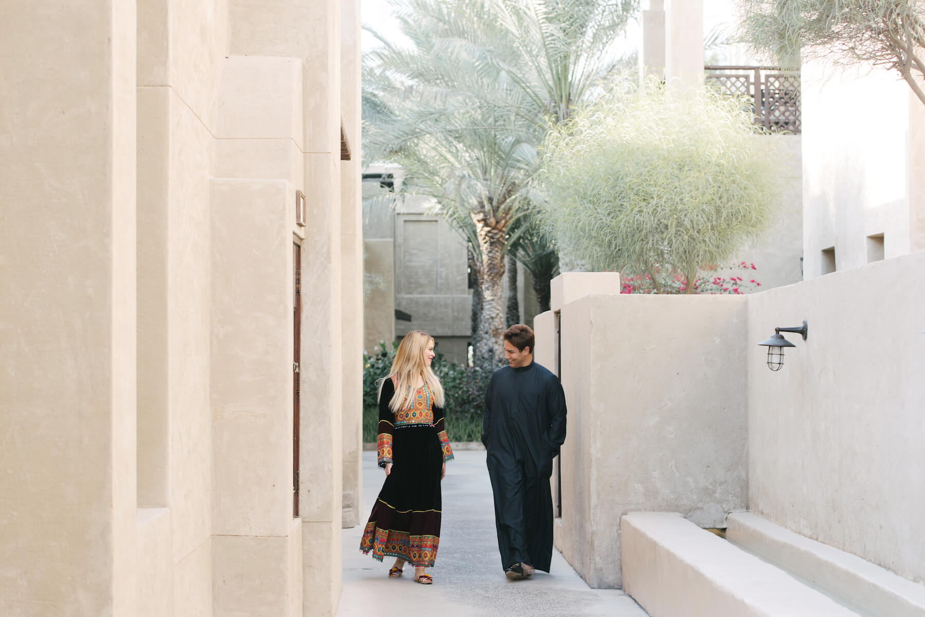Couple holding hands and walking down pathway together surrounded by palm trees at the Dubai Desert Conservation Reserve