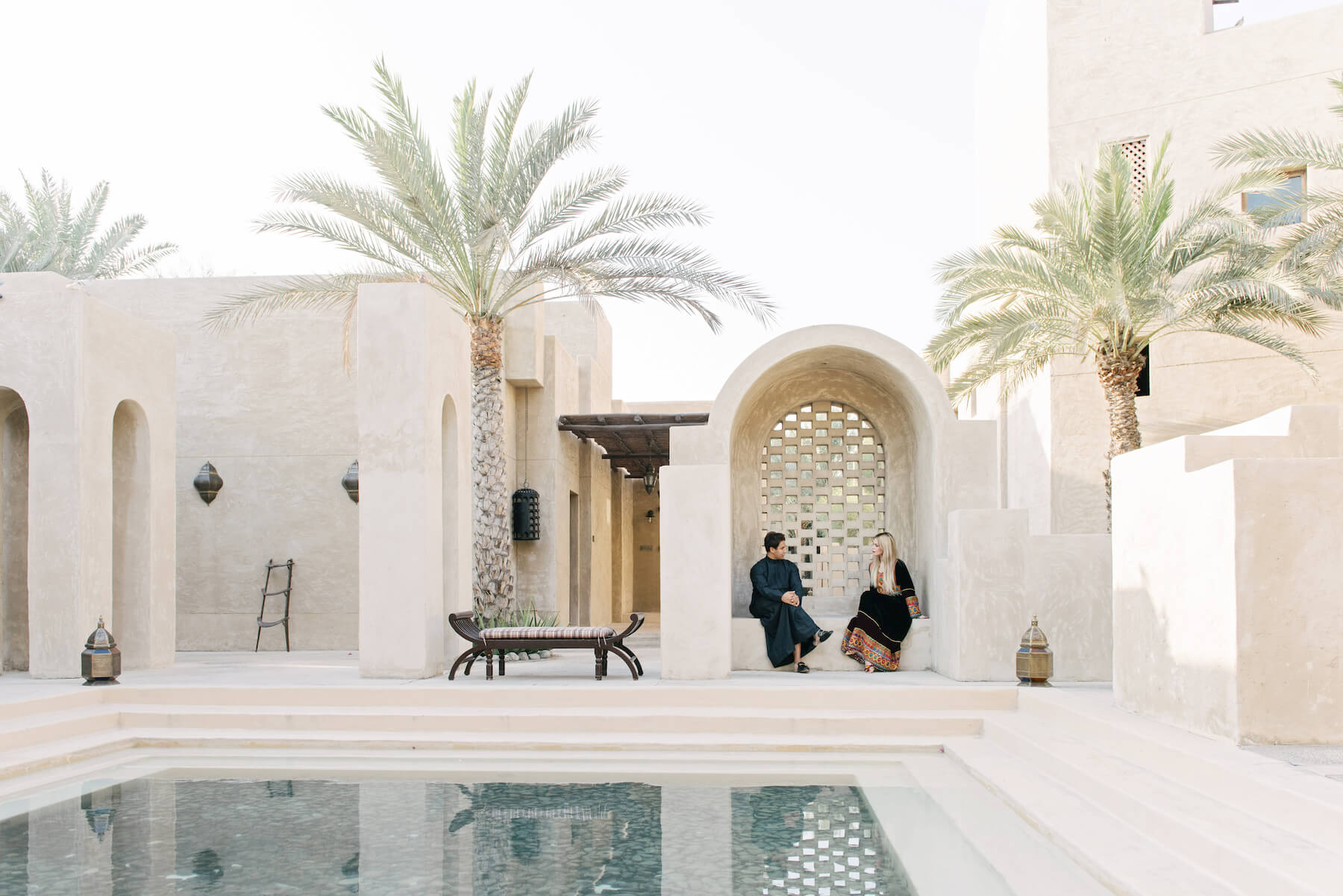 Couple sitting together in an outdoor space beside a pool at the Dubai Desert Conservation Reserve