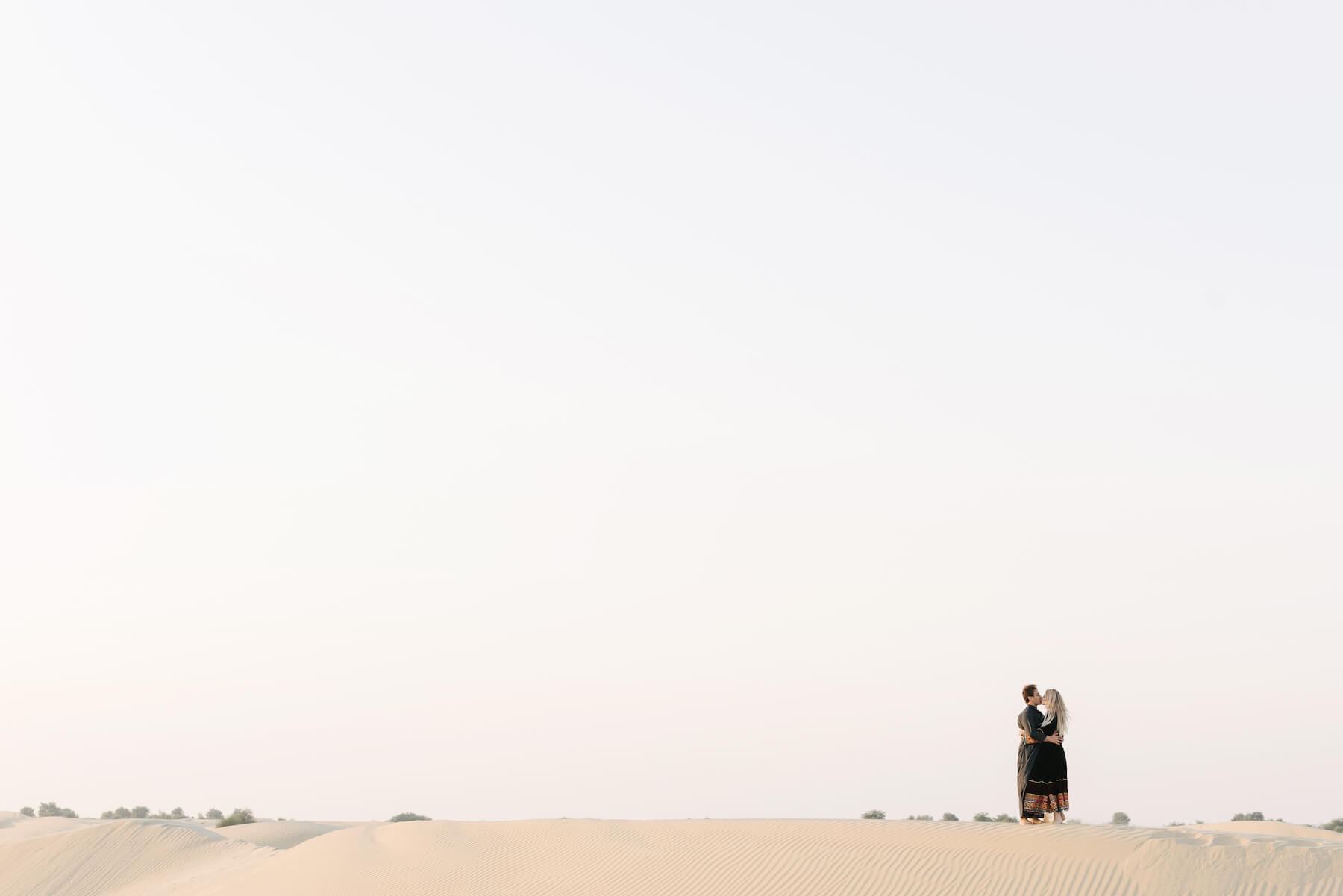 Couple hugging and kissing each other in the desert sands at the Dubai Desert Conservation Reserve