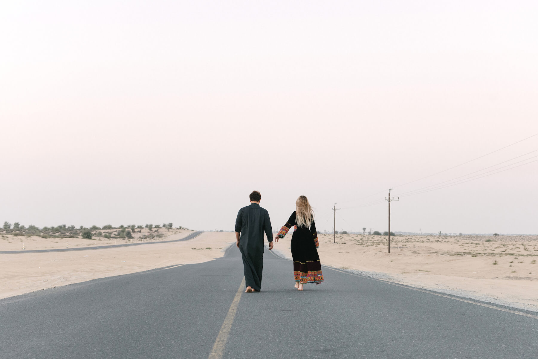 Couple walking down highway road together near the Dubai Desert Conservation Reserve