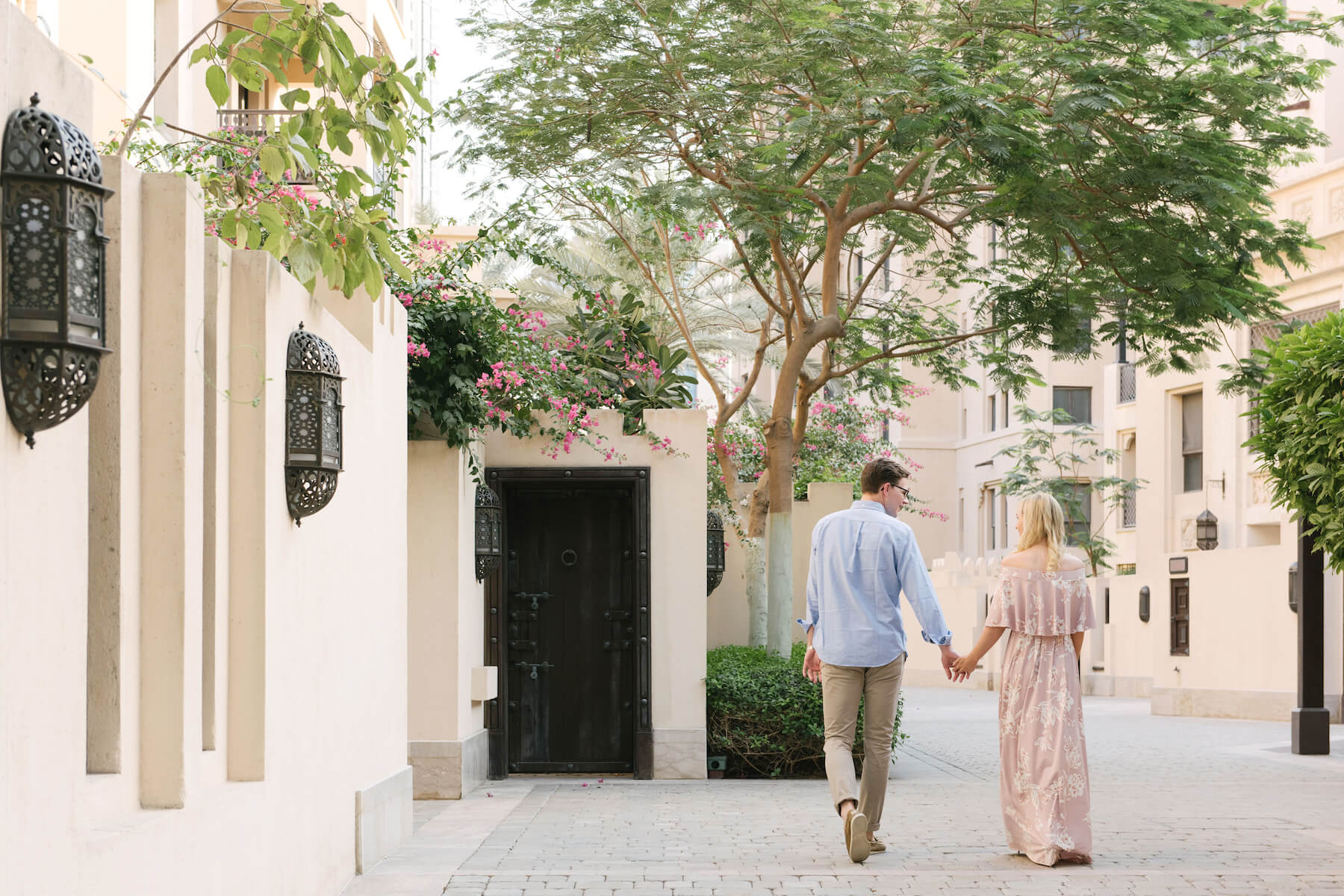 Couple holding hands and walking down alleyway (facing away from the camera) in Old Dubai, Dubai United Arab Emirates