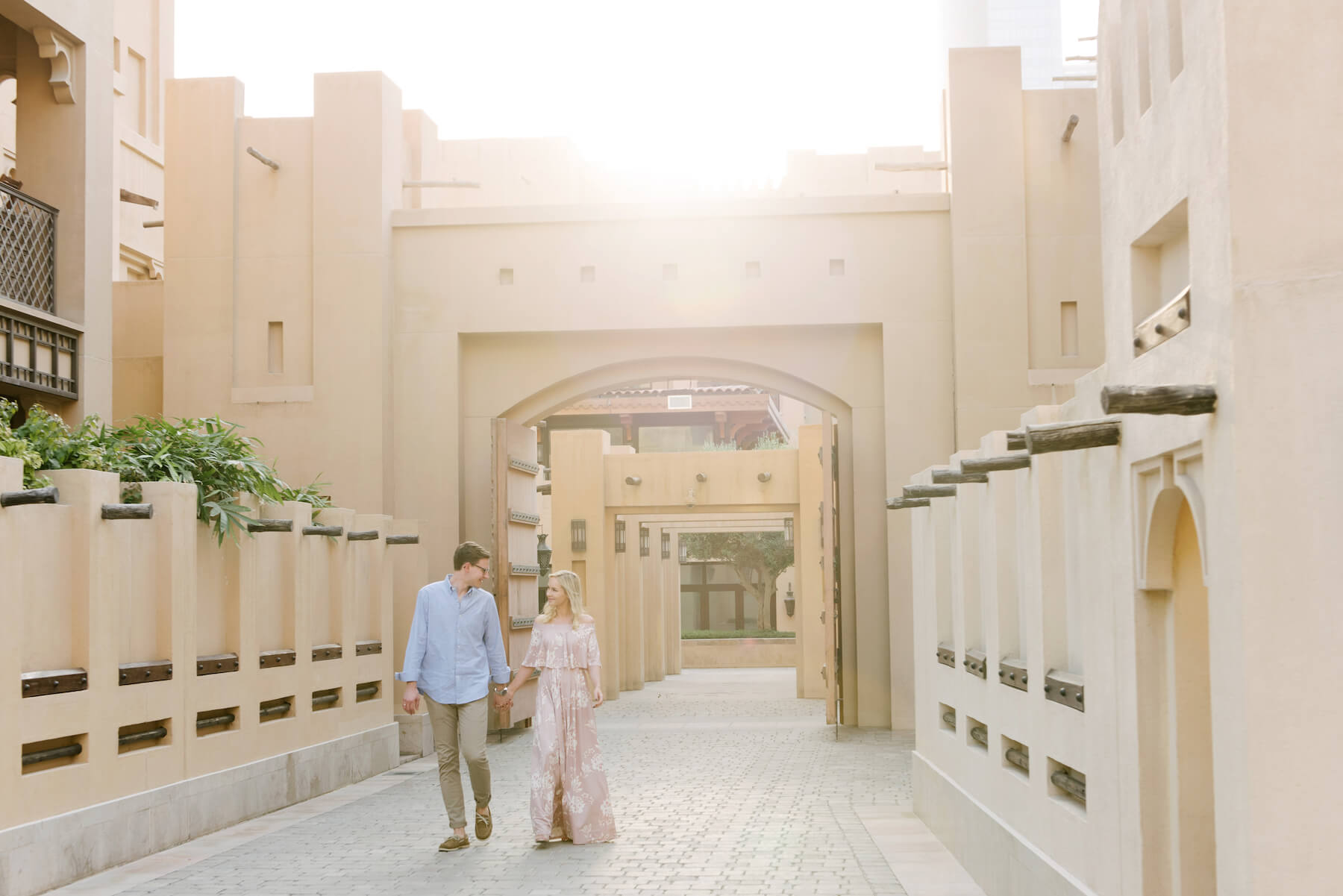 Couple holding hands and walking down alleyway in Old Dubai, Dubai United Arab Emirates