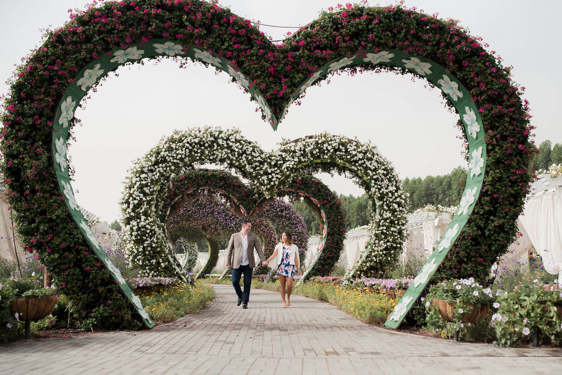 Couple holding hands and walking through heart-shaped floral archways in the Dubai Miracle Garden