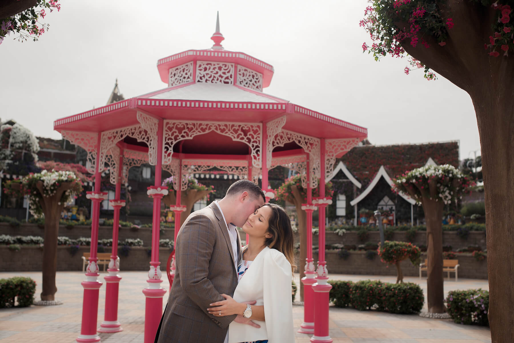 Couple kissing in front of pink gazebo in the Dubai Miracle Garden