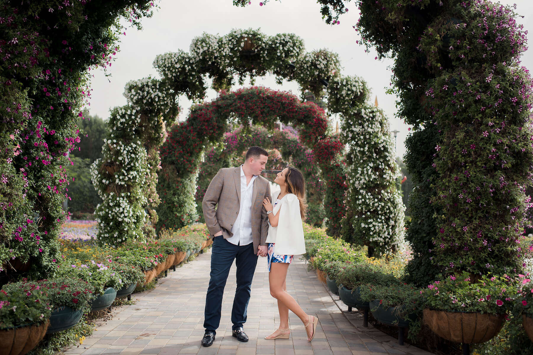 Couple standing together under floral archways at the Dubai Miracle Garden