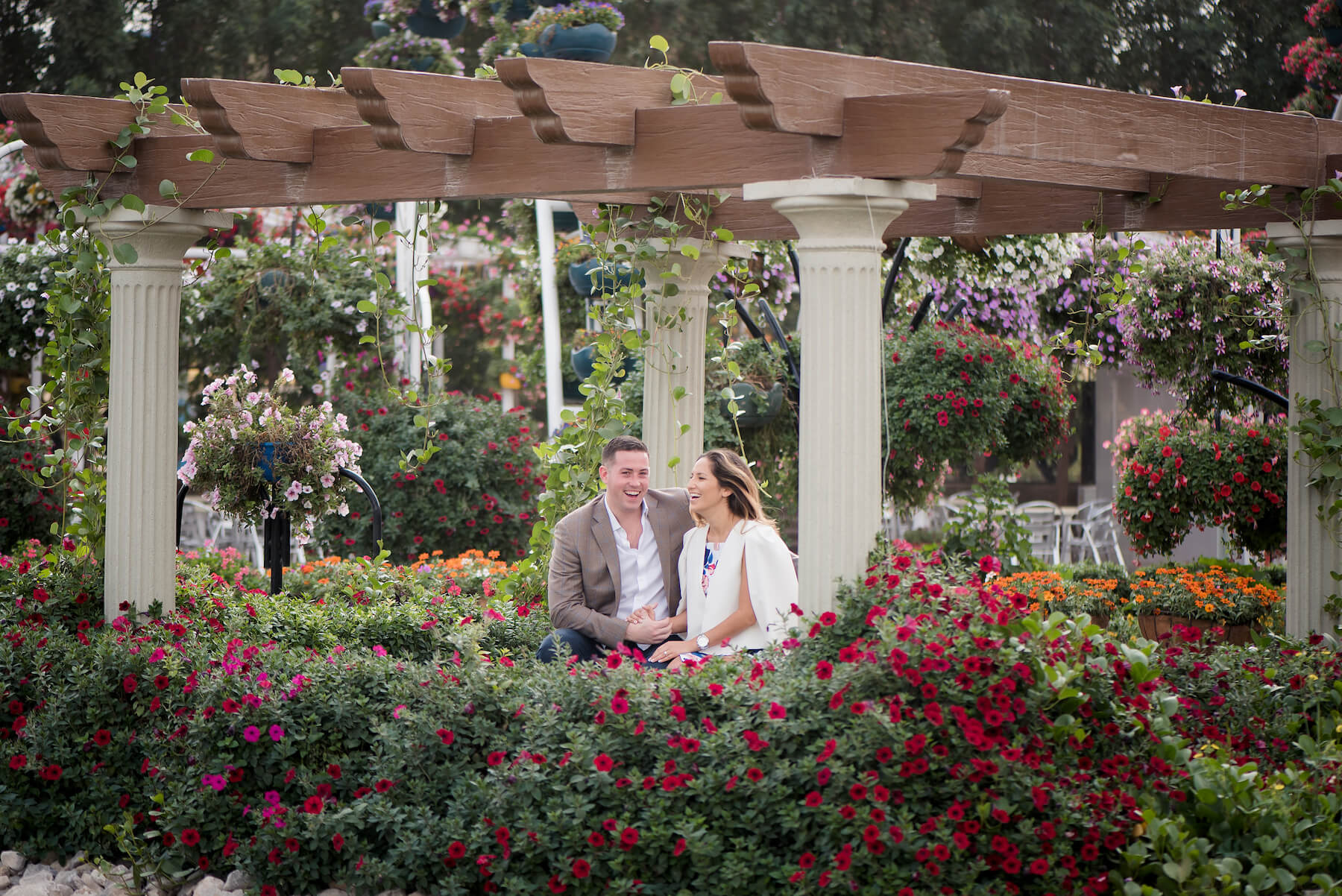 Couple sitting together in a gazebo area amongst many flowers in the Dubai Miracle Garden