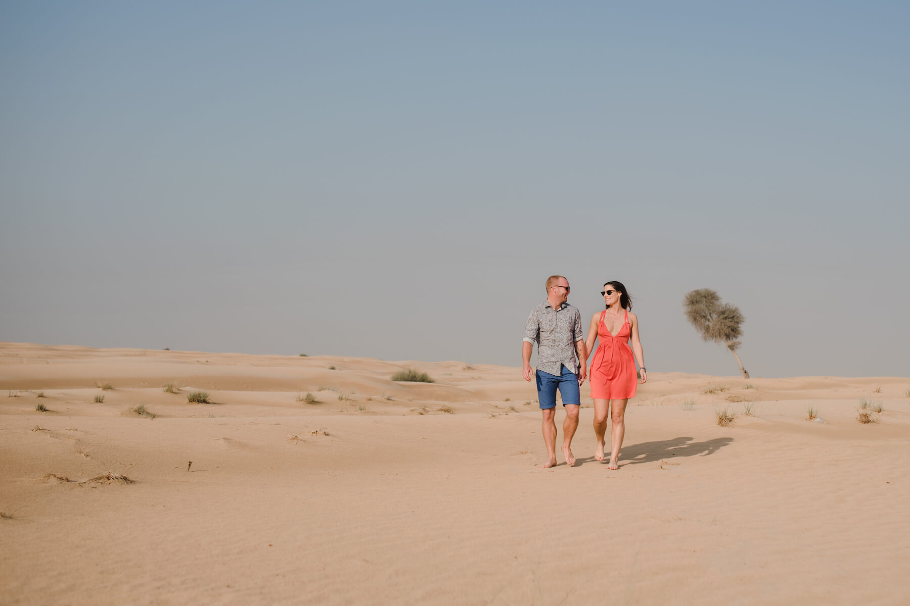 Couple walking together and holding hands in the desert sands of Al Qudra Lake