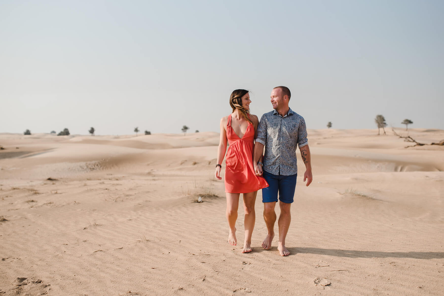 Couple smiling at each other and holding hands in the desert sands of Al Qudra Lake