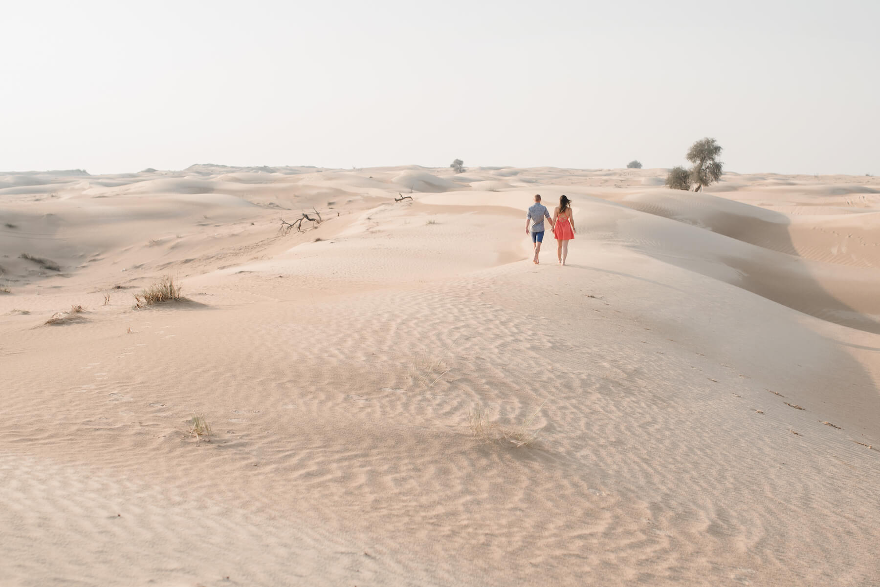Couple walking and holding hands in the desert sands of Al Qudra Lake on a couples trip to Dubai