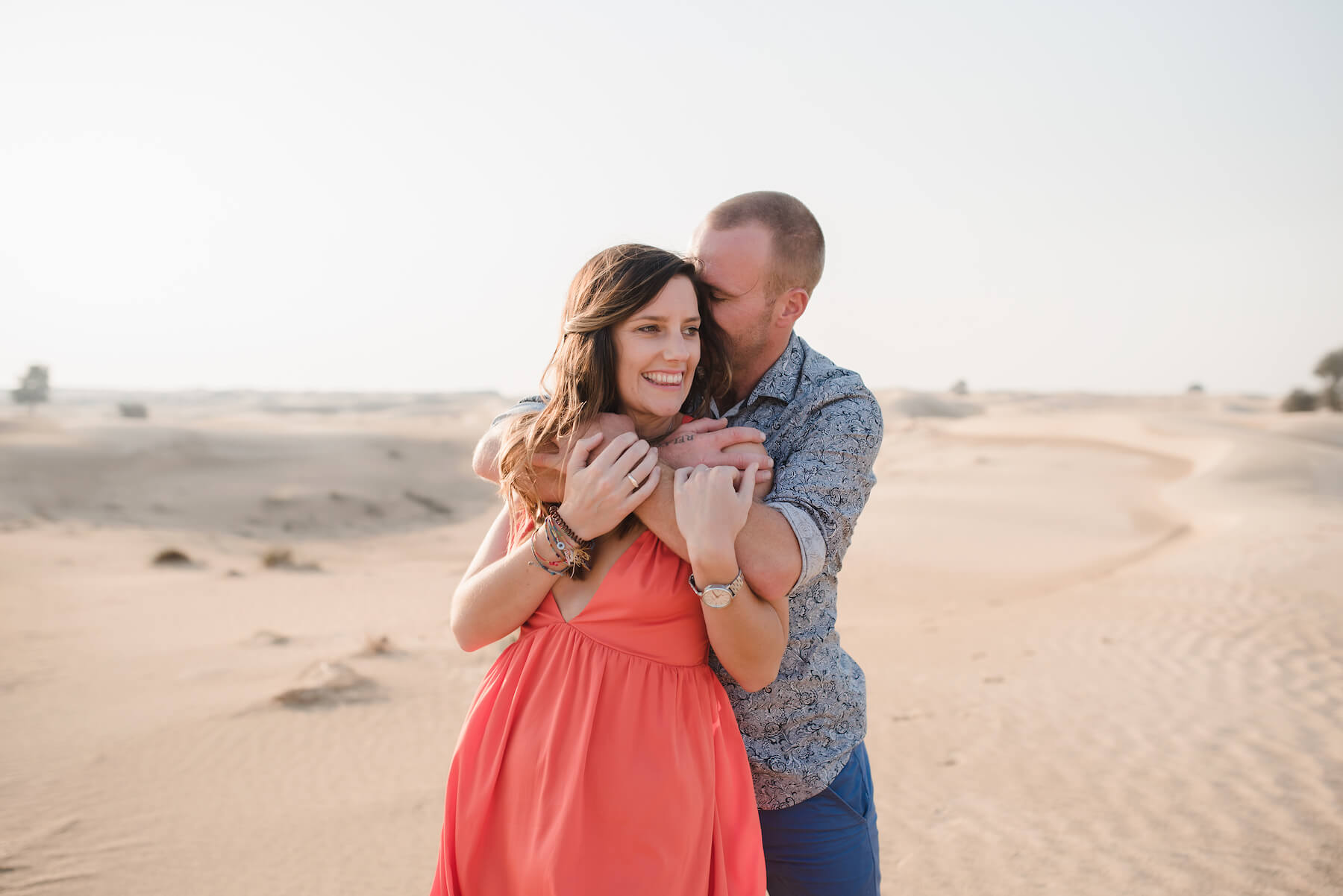 Couple hugging each other in the desert sands of Al Qudra Lake on a couples trip to Dubai